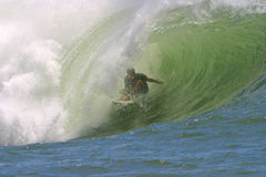 Surfer in the Curl of a Tube Wave. The surfer rides in the curling part of a tubing wave while surfing in Hawaii Royalty Free Stock Photos