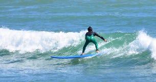 Surfer dans la vague d'équitation de wetsuit Photographie stock