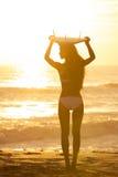 Surfer de bikini de femme et plage de coucher du soleil de planche de surfing Photographie stock