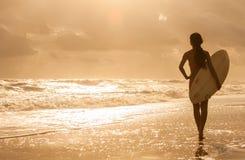 Surfer de bikini de femme et plage de coucher du soleil de planche de surfing Photos libres de droits