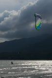 Surfer de cerf-volant et cerf-volant éclairés à contre-jour contre des nuages Photos libres de droits
