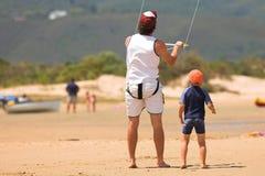 Surfer de cerf-volant sur la plage avec un garçon Images stock