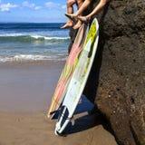 Surfer de deux amis s'asseyant sur la roche Photo stock