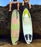 Surfer de deux amis s'asseyant sur la roche Images stock