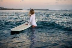 Surfer de femme avec le conseil dans des mains à la plage Photos libres de droits