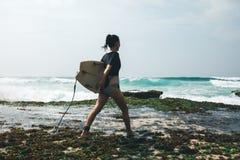 Surfer de femme marchant avec la planche de surf image stock