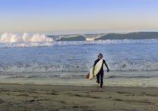 Surfer de garçon marchant hors du ressac d'océan Image libre de droits