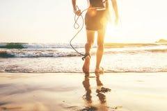 Surfer de jeune homme prenant la planche de surf et venant avec le long panneau de ressac aux vagues sur le fond égalisant de ci photos stock