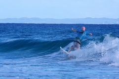 Surfer, der eine kleine Welle in Stradbroke-Insel fängt Lizenzfreie Stockbilder