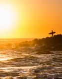 Surfer, der im Punkt mit Surfbrett steht Lizenzfreie Stockfotografie