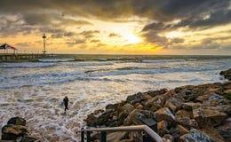 Surfer, der vom Wasser bei Sonnenuntergang herauskommt Lizenzfreie Stockfotos