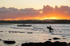 Surfer, der zum Strand am Sonnenuntergang u. an x28 zurückkommt; silhouette& x29; stockbild