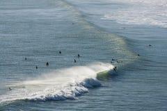 Surfer, die auf Welle an Piha-Strand fahren Stockbilder