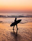Surfer die op een Portugees strand tijdens zonsonderganguren lopen stock foto's