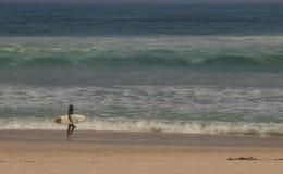 Surfer die op strand op een niet zo prettige dag lopen royalty-vrije stock foto