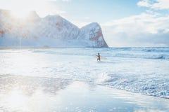 Surfer die tijdens een grijze de winterdag surfen in Lofoten-eiland in Noorwegen stock afbeelding