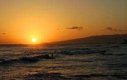 Surfer die tijdens een Hawaiiaanse Zonsondergang surft stock afbeeldingen