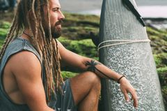 Surfer with dreadlocks and tatoos with surfingboard. Young tanned hipster man with long dreadlocks and beautiful tattoos sitting and watching the ocean on the Stock Image