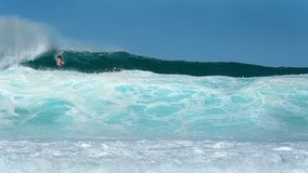 Surfer drops in at Pipeline. Surfer drops into a massive outside set wave, during an epic North swell at Banzai Pipeline in Hawaii Stock Images