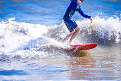 Surfer dude on a surfboard riding ocean wave Stock Images