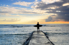 Surfer Enjoying Sunset on Jetty Stock Image