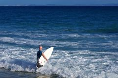 Surfer entering the ocean with his board Stock Photo