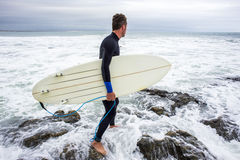 Surfer Entering the Surf with Surfboard Stock Photos