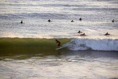 Surfer entrant sur la vague de tube, sports aquatiques, crépuscule Images libres de droits