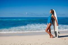 Surfer féminin dans des vêtements de bain bleus avec le conseil dans des mains sur le littoral Image stock