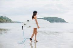 surfer féminin dans la planche de surf et aller de participation de bikini images libres de droits