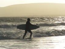 Surfer faisant un pas hors de l'océan Photos stock