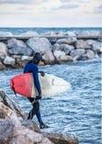 Surfer faisant un pas sur la mer avec le conseil rouge et blanc photos libres de droits