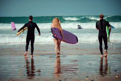 Surfer friends on a beach with a surfing boards Stock Images