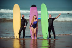 Surfer friends on a beach with a surfing boards.  Royalty Free Stock Images