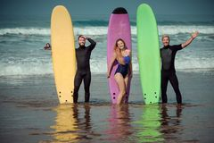 Surfer friends on a beach with a surfing boards Stock Photography