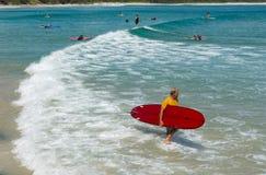 Surfer geht in den Strand von Byron Bay Stockfotos