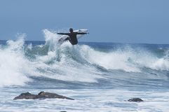 Surfer getting Air. Surfer catapulting out of wave Stock Photo