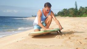 A surfer waxing board before surfing Hawaii