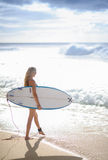 Surfer girl 1. A Beautiful woman walking with surfboard on a beach with waves breaking in the background Stock Images