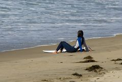 Surfer girl 2. A young woman is sitting on the beach looking at the surf Royalty Free Stock Images