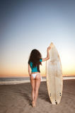 Surfer Girl. Beautiful model wearing a white bikini and surfer outft holding a surfboard during sunset by the beach Stock Photography