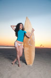Surfer Girl. Beautiful model wearing a white bikini and surfer outft holding a surfboard during sunset by the beach Royalty Free Stock Images