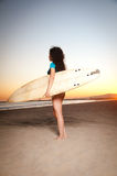Surfer Girl. Beautiful model wearing a white bikini and surfer outft holding a surfboard during sunset by the beach Stock Photo