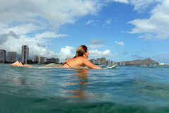 Surfer girl. A bikini surfer teen girl paddling out royalty free stock images