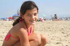 Surfer Girl. Girl sitting on her surf board on the sand Stock Image