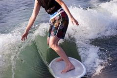 Surfer Girl. A girl riding a surfboard in the wake behind a boat royalty free stock images