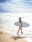 Surfer girl 6. A Beautiful woman walking with surfboard on a beach with waves breaking in the background 6 Stock Photos