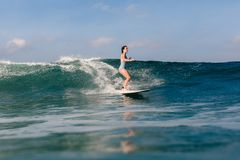 Young woman in bright bikini surfing on a board in ocean stock photography