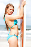 Surfer girl on the beach in bikini. Royalty Free Stock Images