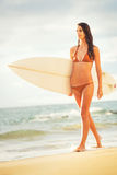 Surfer Girl on the Beach at Sunset Royalty Free Stock Images